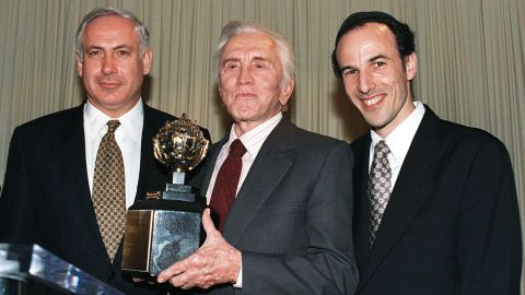 """Actor Kirk Douglas holds the King David Award, presented to him by the Jerusalem Fund of Aish HaTorah during a dinner in Beverly Hills, California, on November 17, 1997. Douglas was honored for his inspirational commitment to Israel and the Jewish people and in recognition of his new book """"Climbing the Mountain."""" Netanyahu is on the left. To the right is Rabbi Nachum Braverman, director of the Jerusalem Fund of Aish HaTorah."""