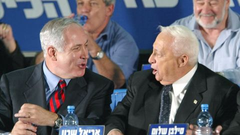 Netanyahu, as Israel's foreign minister, laughs with Israeli Prime Minister Ariel Sharon at the start of a Likud convention in Tel Aviv on November 12, 2002.
