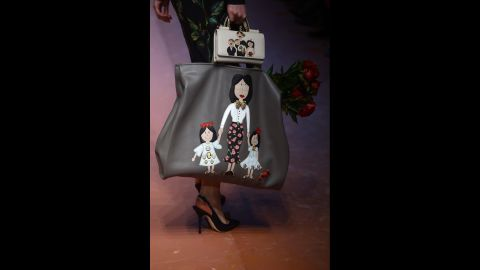 A model carries bags featuring embellished family drawings for Dolce & Gabbana's fall/winter collection.