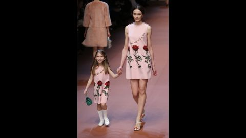 """A mother and daughter wear matching dresses down the runway. The writing on the dresses reads, """"I love you, mom."""""""