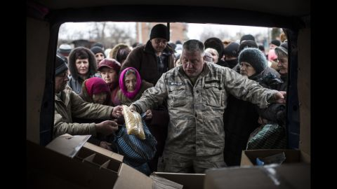 A volunteer gives humanitarian aid to residents of Popasna, Ukraine, on Saturday, February 28.