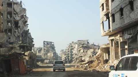 On 24 January 2015 in the Syrian Arab Republic, vehicles of the United Nations travel a dusty road lined with the rubble remnants of destroyed buildings, in the Old City of Homs, Homs Governorate. One of the vehicles bears the UNICEF logo.