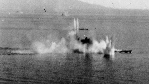 The Japanese battleship Musashi under intense attack by Task Force 38 aircraft in the Sibuyan Sea. A destroyer is also receiving attacks beyond the battleship.