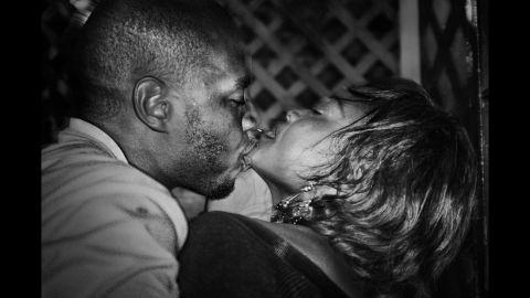 A young man kisses his girlfriend at a bar of the Ewa Bora suburbs of Lubumbashi.