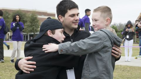 Manero's team has made electronic arms for five children and are working with three more kids including 12-year-old Wyatt Falardeau, left, who lost his right arm to amputation when he was a baby. He shares a hug with Alex and Manero at UCF.