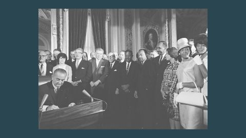 President Lyndon B. Johnson signs the Voting Rights Act in 1965 as the Rev. Martin Luther King Jr. looks on.