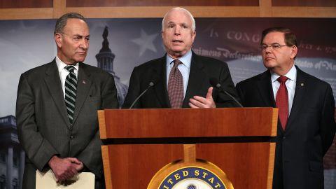 Sen. John McCain (R-AZ) (center) speaks as Sen. Charles Schumer (D-NY) (left) and Sen. Robert Menendez (D-NJ) (right) listen during a news conference on a comprehensive immigration reform framework January 28, 2013 on Capitol Hill in Washington.