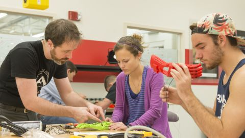 """Ivan Owen, co-designer of the first 3D printed prosthetic hand and a designer for the <a href=""""http://enablingthefuture.org/"""" target=""""_blank"""" target=""""_blank"""">E-Nable community</a>, instructs students at a Build-a-Thon at the University of Central Florida. The students produced 60 robotic hands for a pediatric rehab clinic in San Antonio, Texas."""