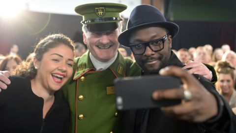 Musician will.i.am, right, surprised staff at the Harrods department store in London on Thursday, March 5.