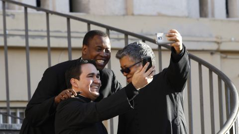 Priests in Rome snap selfies as they wait for the arrival of Pope Francis on Saturday, March 7.