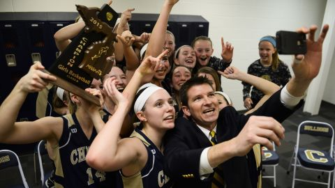 Todd Blomquist, head coach of the Chelsea High School girls basketball team, takes a selfie with the team after winning the district championship Friday, March 6, in Chelsea, Michigan.