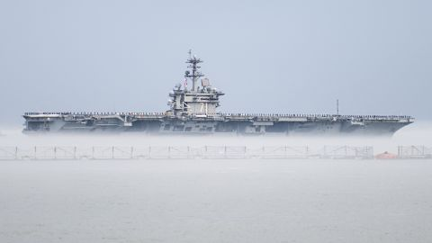 The aircraft carrier USS Theodore Roosevelt departs Naval Station Norfolk, Virginia, on Wednesday, March 11, for a scheduled deployment. The Nimitz-class carrier's departure was delayed for two days after marine growth clogged sea water intakes. Divers went into the 36-degree water to clean out the intakes and allow the ship to get under way. The cold water created a fog that made it seem the ship was in a cloud.