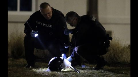 Police shine a light on a helmet as they investigate the scene outside the Ferguson Police Department on March 12.
