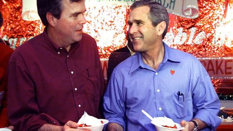 Then-President George W. Bush (right) and Jeb Bush go through the line for strawberries during a stop at the Stawberry Festival March 12, 2000 in Plant City, Florida.