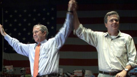 Then-President George W. Bush (left) and Jeb Bush (right), raise their arms onstage following a rally at the Florida State Fairgrounds, October 25, 2000, in Brandon, Florida.
