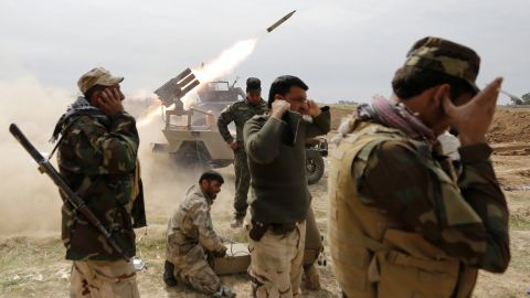 Iraqi Shiite fighters cover their ears as a rocket is launched during a clash with ISIS militants in the town of Al-Alam, Iraq, on Monday, March 9.