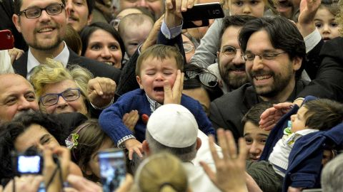 Pope Francis touches a child's face as he arrives for a meeting at the Vatican on Friday, March 6, 2015.