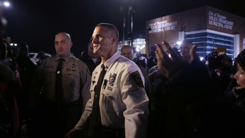 """St. Louis County police Lt. Jerry Lohr walks through a crowd of protesters in Ferguson on March 12, trying to get them to move out of the street. The St. Louis County police said it had assumed """"command of the security detail regarding protests,"""" together with the Missouri State Highway Patrol."""
