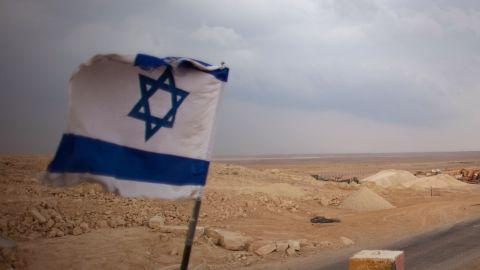 An Israeli flag flies at a desert checkpoint