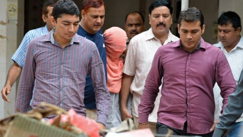 Indian policemen escort the juvenile (C, in pink hood), accused in the December 2012 gang-rape of a student, following his guilty verdict at a court in New Delhi on August 31, 2013. An Indian court found a teenager guilty August 31 over the fatal gang-rape of a student in New Delhi, a crime that sparked revulsion and angry protests in the country, an official said. AFP PHOTO/Prakash SINGH
