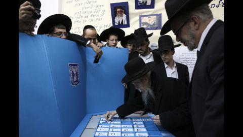 Rabbi Gershon Edelstein, center, prepares to vote in Bnei Brak, Israel, on March 17.