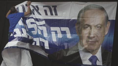 A man hangs a poster of Netanyahu at his election campaign headquarters in Tel Aviv on March 17.