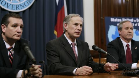 Governor Greg Abbott (center) speaks alongside Cruz (left), Attorney General Ken Paxton (right) at a joint press conference February 18, 2015, in Austin, Texas.