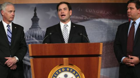 Rubio, center, speaks to members of the media as Sen. Ron Johnson, left, and Rep. Ron DeSantis listen during a news conference on Capitol Hill in October 2013.