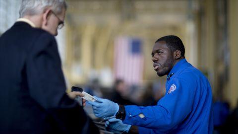 A TSA officer hands a passenger his identification at a security checkpoint at Ronald Reagan National Airport in Washington.
