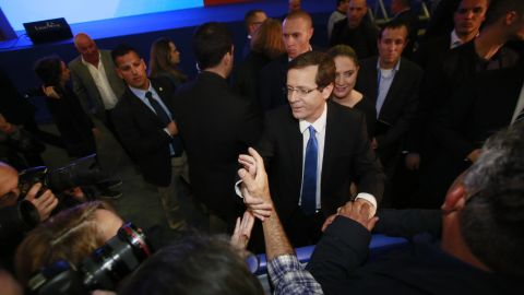 Isaac Herzog, co-leader of the Zionist Union alliance, shakes hands with supporters in Tel Aviv as he reacts to exit poll figures on Tuesday, March 17.