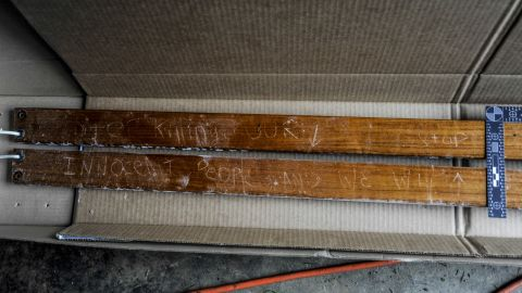 """Prosecutors said these boards were attached to the boat where police found Dzhokhar Tsarnaev hiding. A carved message reads, """"Stop killing our innocent people and we will stop."""""""