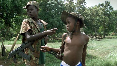 Two children enrolled with Sierra Leone troops battling rebels of the Revolutionary United Front get ready to fight east of the capital of Freetown in May 2000.