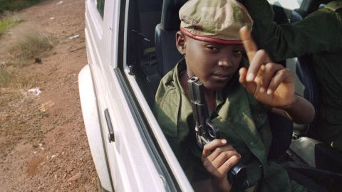A child with a gun sits in a car with Rwandan Patriotic Front partisans patrolling the streets of Kigali, Rwanda, in June 1994.