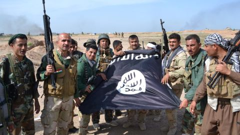Iraqi Kurdish Peshmerga fighters pose for a photo with an ISIS flag in the village of Sultan Mari, west of the city of Kirkuk, in March 2015.