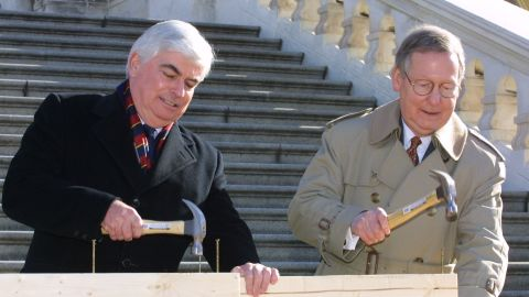 """Sen. Christopher Dodd, D-Connecticut, and McConnell hammer the """"first nails"""" into a piece of wood during a nail-driving ceremony in December 2000 on Capitol Hill. Both senators participated in the ceremony to signify the beginning of construction of the 2001 Inaugural platform on the West Front Terrace of the U.S. Capitol."""