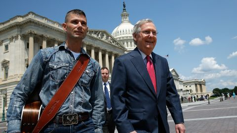 """McConnell walks with """"America's Got Talent"""" contestant Jimmy Rose to a news conference on the economic ramifications of the Environmental Protection Agency's proposed power plant rules in July 2014."""