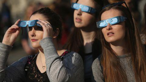 People look into the sky near the Brandenburg Gate in Berlin, Germany.