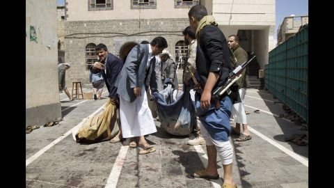 Houthi fighters carry the body of a man killed in Sanaa on March 20.