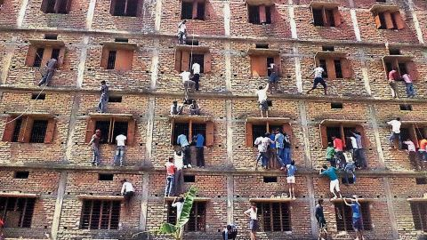 Indians climb the wall of a building to help students in an examination in Hajipur, Bihar, on Wednesday, March 18, 2015.