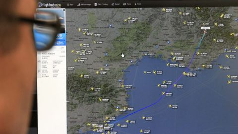 A man in Madrid looks at a monitor with a map, released from the Flightradar24 website, showing the point where the plane's radar signal went missing.