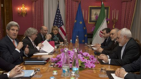 United States Secretary of State John Kerry (L) sits with his delegation during a negotiation meeting concerning Iran's nuclear program with Iran's Foreign Minister Javad Zarif (R) in Lausanne on March 19, 2015 as European Union Political Director Helga Schmid (4-L) looks onover.