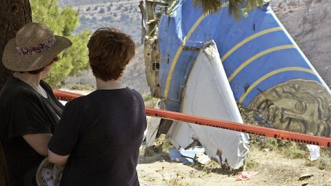 Women look at the debris of the Cypriot Helios airliner which crashed August 13, 2005 at Grammmatiko hills near Athens.
