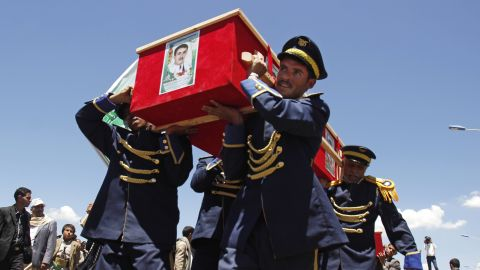 """On March 25, honor guards in Sanaa carry the coffins of victims who were killed in<a href=""""http://www.cnn.com/2015/03/20/world/gallery/yemen-attack/index.html"""" target=""""_blank""""> suicide bombing attacks</a> several days earlier. Deadly explosions in Sanaa rocked two mosques serving the Zaidi sect of Shiite Islam, which is followed by the Houthi rebels that took over the capital city in January."""