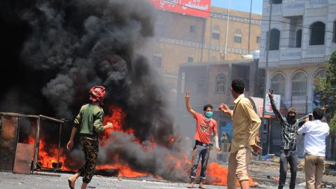 Yemenis stand in front of burning tires during an anti-Houthi protest in Taiz, Yemen, on Tuesday, March 24.