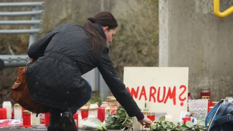 A woman lights a candle next to a sign reading: 'Why?' at the Joseph-Koenig-Gymnasium in Haltern, Germany.