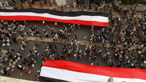 """Houthi supporters in Sanaa deploy giant national flags Wednesday, March 18, during a demonstration to mark the fourth anniversary of the """"Friday of Dignity"""" attack. In 2011, forces loyal to Saleh <a href=""""http://www.cnn.com/2011/10/15/world/meast/yemen-unrest/"""" target=""""_blank"""">opened fire on protesters</a> who had gathered in Sanaa to demand the ouster of Saleh and his regime."""