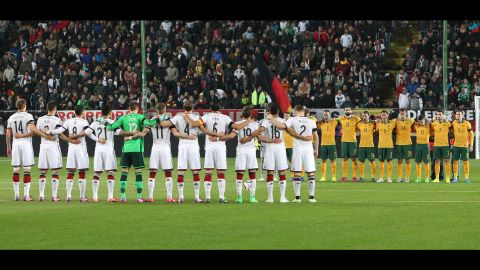 Members of the German and Australian national soccer teams observe a moment of silence before a friendly match in Kaiserslautern, Germany, on March 25.
