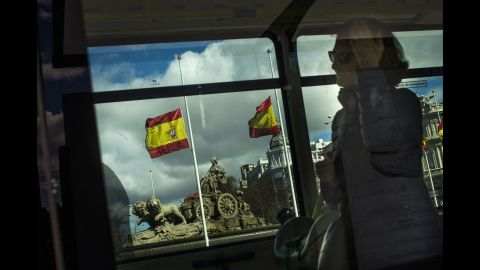 A woman uses public transit in Madrid as flags fly at half-staff on March 25.