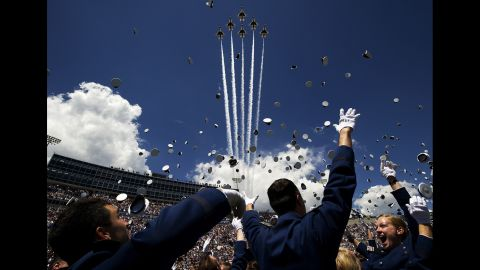 Air Force cadets toss their caps in the air as U.S. Air Force Thunderbirds fly in Delta formation overhead during the U.S. Air Force Academy's graduation ceremony May 28, 2014, in Colorado Springs, Colorado.