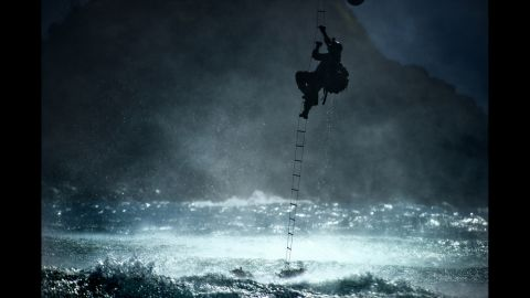 A 22nd Special Tactics Squadron airman climbs a ladder into a CH-47 Chinook helicopter hovering over the ocean on June 20, 2014.